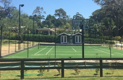 A backyard tennis court looking front on